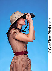 Woman in safari hat looking through binoculars side view - A...