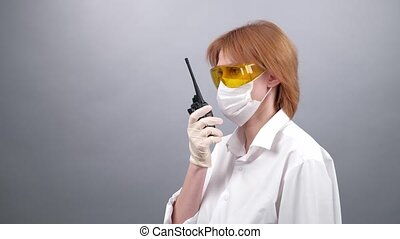 woman in safety glasses, medical mask and rubber gloves speaks on the walkie-talkie or talking on a portable radio set