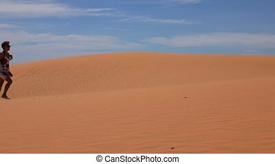 Woman in sand dunes - Young woman walking across the sand...