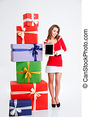 Woman in santa claus cloth showing blank computer screen