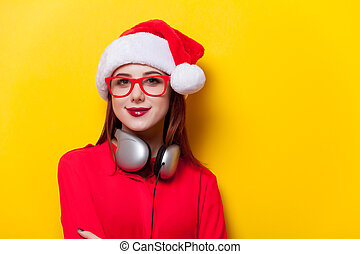 woman in Santa Claus hat with headphones