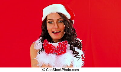 Woman in Santa hat blowing Xmas snowflake. Red background.