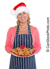Woman in Santa hat holding a plate of gingerbread men