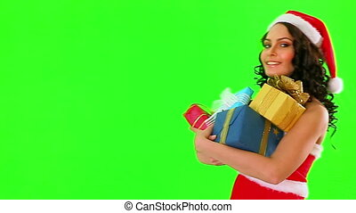 Woman in Santa hat holding gift box. Used tripod. Green background.