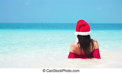 Woman in santa hat in bikini at tropical beach. Slow motion.