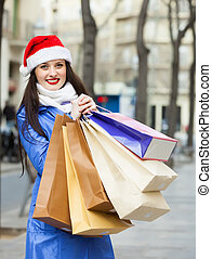 woman in Santa hat with purchases