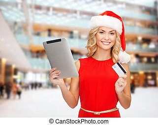 woman in santa hat with tablet pc and credit card
