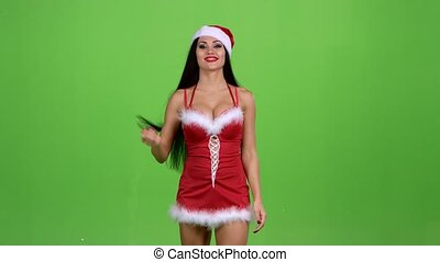 Woman in Santas costume is walking and sexually bewitching...