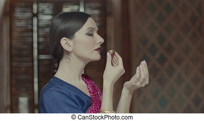 Woman in sari sniffing delicious sachet aroma - Side view of...