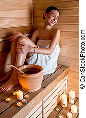 Woman in sauna - Young woman in white towel resting in...