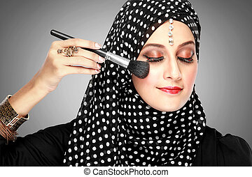 portrait of young beautiful woman with brush for make-up. applying blush on