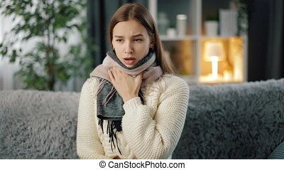 Young sick woman in knitted scarf coughing on grey couch. Pretty female with brown hair suffering from sore throat while staying at home.