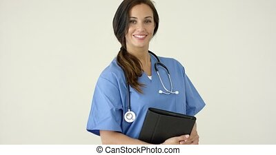 Woman in scrubs holds black portfolio and smiles at camera...
