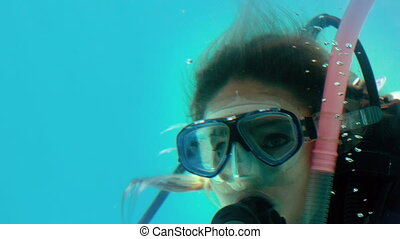 Woman in scuba gear looking at camera