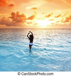 Woman in sea on sunset
