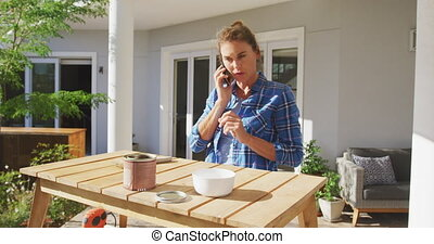 A Caucasian woman spending in her garden, renovating her house, social distancing and self isolation in quarantine lockdown during coronavirus covid 19 epidemic, talking on a smartphone in slow motion