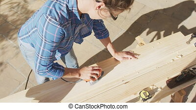 A Caucasian woman in her garden, renovating her house, social distancing and self isolation in quarantine lockdown during coronavirus covid 19 epidemic, sanding a wooden plank with an electric drill