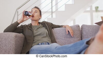 A Caucasian woman spending time at home, social distancing and self isolation in quarantine lockdown during coronavirus covid 19 epidemic, sitting on a sofa, holding a bottle and drinking