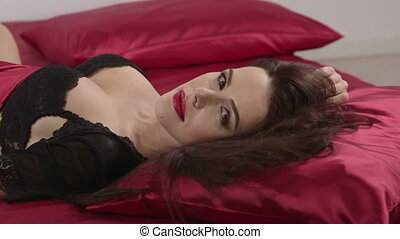 Woman in sexy black lingerie lying on red linen in bed looking at camera