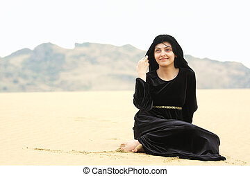 Woman in shawl sitting on sand