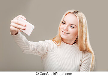Woman in shirt making selfie. gray background
