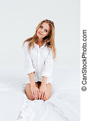Woman in shirt sitting on bed and looking at camera