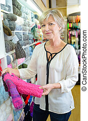 Woman in shop looking at knitted child's clothing