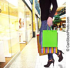 Woman in shopping center doing window shopping