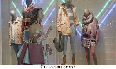 Woman in shopping center with bags. Fashion girl in mall looking on shopwindow background.