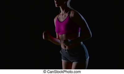 Woman in shorts and top runs beautifully on a black screen....