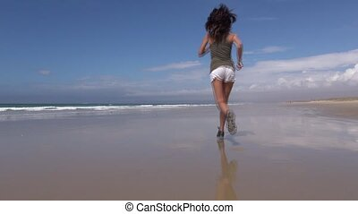 woman in shorts jogging at beach