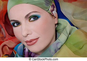 Portrait of attractive woman with bright makeup in silk head scarf