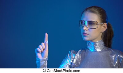 Woman in silver clothing wearing eyeglasses pressing virtual buttons