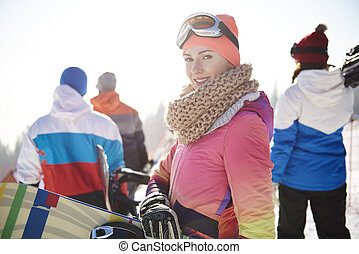 Woman in ski clothes with friends on the background