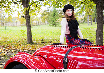 Woman in skirt on red car cowling - Young woman in skirt on ...