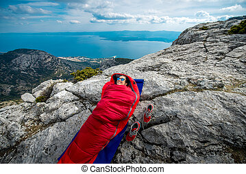 Woman in sleeping bag on the mountain - Young woman lying in...