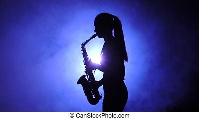 Woman in smoky studio plays on saxophone, silhouette. Slow...