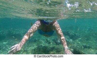 Woman in snorkel diving and waving with hands