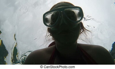 woman in snorkling mask swimming underwater, silhouette beautiful