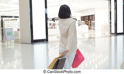 Woman in soft colored jeans and jacket walking and spinning at the mall while carrying shopping bags in both hands.
