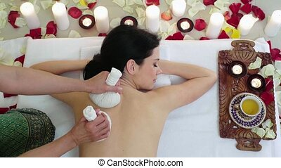 Woman in Spa Resort Massage Aromatic Herbs Bags