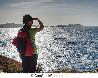 Woman in sports clothes shadowing eyes  at sea