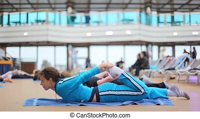 woman in sports hall does gymnastics with others lying on rug