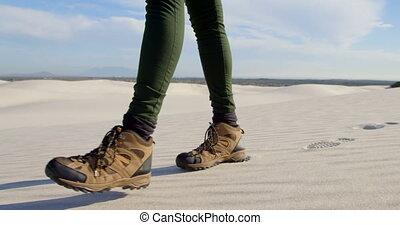 Woman in sports shoes walking in the desert 4k - Woman in...