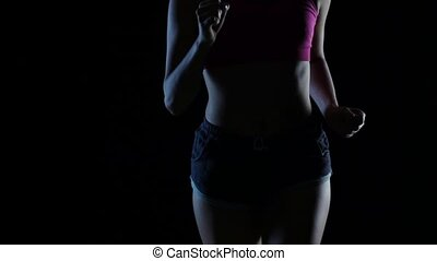 Woman in sports wear running on a black screen. Silhouette. Slow motion. Close up