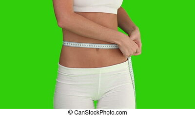 Chromakey footage of a woman in sportswear checking her weight