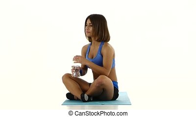 Woman in sportswear drinking water from bottle. White