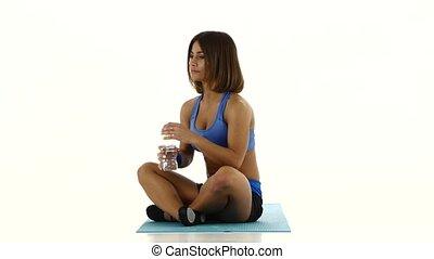 Woman in sportswear drinking water from bottle. White