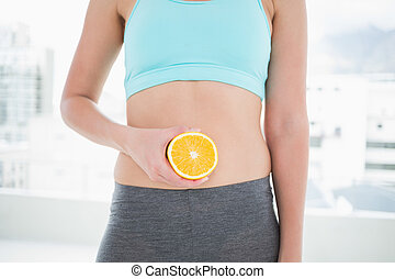 Woman in sportswear holding orange