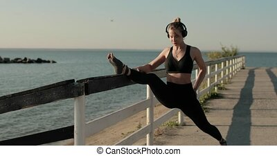 Woman in sportswear is stretching leg putting it on fence on river waterfront.